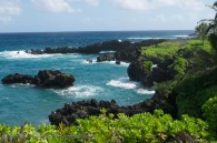 tropical shoreline with lava rocks and clear ocean water surf