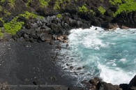 black sand beach in small cove, waves breaking on the shore