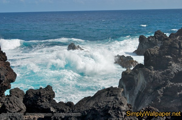 surf along the shoreline with lava rocks