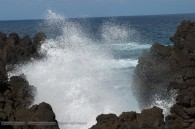 ocean wave crashing on shoreline of rough lava rocks