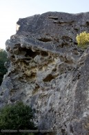 large rock outcropping with holes like swiss cheese