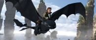 a black night fury dragon named toothless flies over the water with his rider hiccup