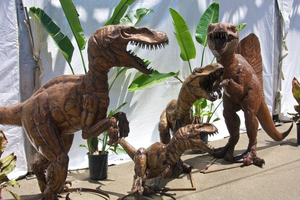 a collection of life sized metal sculptures/statues of bipedal dinosaurs
