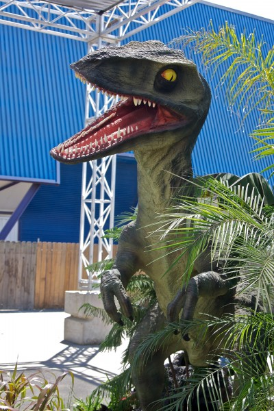 a life sized dinosaur lurks in the bushes