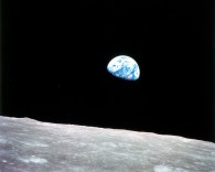 view of the earth rising above the surface of the moon