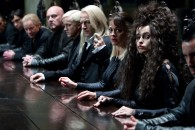 witches and wizards sit at a long table in a scene from Harry Potter and the Deathly Hallows