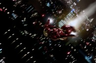 Iron Man flying over a night cityscape