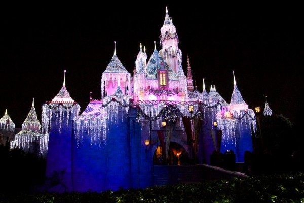 night time picture of Sleeping Beauty castle at Disneyland decorated for Christmas wallpaper